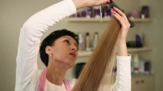 Close up view of professional hairdresser cutting long blond girls hair with scissors in beauty salon. Stylist doing hairstyle