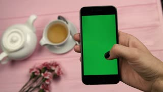 Close up view of womans hand, finger scrolling pages, feed on mobile phone with green screen on pink wooden table. View from above. Chroma key