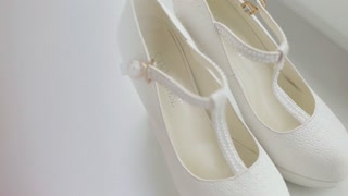Close up white bridal shoes. White wedding shoes on high heels. Woman high heels