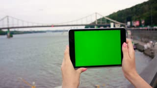 Girl hands holding tablet device with green screen touchscreen. River with bridge and boat background. Chroma key. Close up.