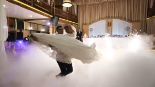 Groom and bride dancing their first dance together on wedding day. Slow motion shotю Cold fountains background