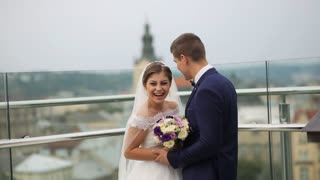 Groom and bride standing in front of the old city landscape on the rooftop. Bride laughing. Lviv, Ukraine. Beautiful city view