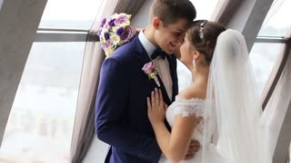Groom and bride with flower bouquet kissing and looking at the camera in front of the window indoor. Beautiful wedding dress. Just married Slow motion shot