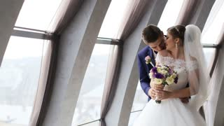 Groom and bride with flower bouquet kissing in front of the window indoor. Beautiful wedding dress. Just married Slow motion shot