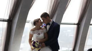 Groom and bride with flower bouquet kissing in front of the window indoor. Slow motion shot