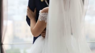 Groom and bride with flower bouquet looking on each other and kissing in front of the window indoor. Beautiful wedding dress. Just married. Slow motion shot