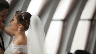 Groom and bride with flower bouquet looking on each other in front of the window indoor. Beautiful wedding dress. Just married Slow motion shot