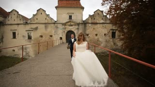 Groom following bride on the pathway near the old castle. Happy couple
