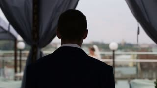 Grooms back silhouette . Groom looking at the city landscape. Lviv. Ukraine. Landscape view of the city from above. Beautiful old city buildings. Antique