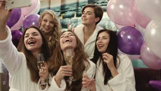 Group of beautiful girls sitting at the beauty salon and taking selfies. Smiling women having good time in spa salon.