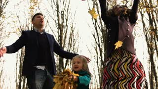 Happy young family having good time playing in fallen leaves in the autmn park