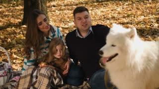 Happy young family with white somoyed dog spending time outdoor in the autumn park. Picnic family time