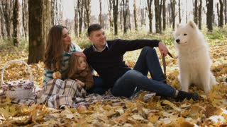 Joyful young family with their daughter spending time outdoor in the autumn park with white somoyed dog.