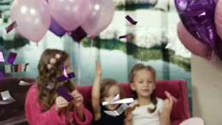 Little girls sitting on the sofa, eating cookies. Celebrating and having fun. Smiling girls having good time at the paty with baloons. Happy birthday. Celebration