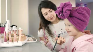 Make up artist applying make up with brush to pretty little girl in white salon. Smiling little girl in pink robe and towel on her head