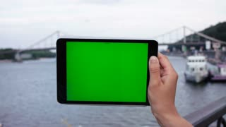 Man holding tablet device with green screen touchscreen. River with bridge and boat background. Chroma key. Close up.
