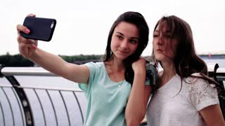 Portrait of young pretty girls smiling and looking at the camera near the river. Young women taking selfies. making funny faces. River background. Taking pictures on smart phone