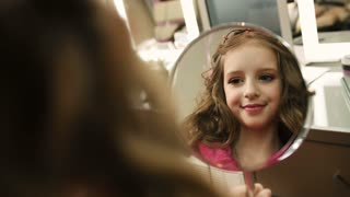 Pretty little girl with curly hair looking at the mirror in the beauty salon. View in the mirror