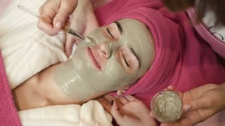 Professional master applying clay on womans face in spa salon. Procedure of face massage in beauty salon. Face care. Treatment. Close up