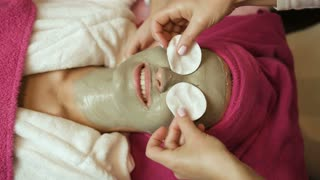 Professional master putting cotton pads on womans face with clay in spa salon. Face care. Treatment. Close up