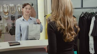Shop assistant giving shopping bag to happy blond woman castomer in fashion showroom