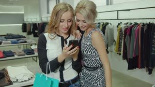 Two beautiful blond women with shopping bags using mobile phone in fashion store