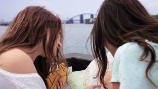 Two young pretty girls looking at the paper map. Women looking for interesting places while traveling. Dnipro river, bridge background. Close up. Back view