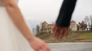 Wedding couple holding hands on olod castle with lake background. slow motion