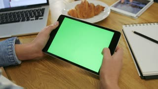 Woman hands using digital tablet touchscreen device with green screen in cafe. Woman scrolling photos, news, pages on tablet computer. Close-up. Chroma key