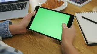 Woman hands using digital tablet touchscreen device with green screen in cafe. Woman scrolling photos, news, pages on tablet computer. top view. Close-up. Chroma key