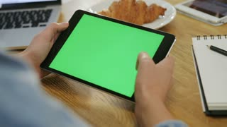 Woman hands using tablet touchscreen device with green screen in cafe. Woman scrolling photos, news, pages on tablet computer. Close-up. Chroma key