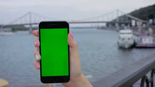 Woman holding smart phone with green screen touchscreen. River with bridge background. Chroma key. Close up shot