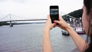 Woman taking pictures, photos and video footages of Dnipro river. Beautiful nature. Hands holding smart phone and making pictures