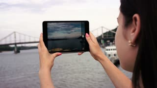 Woman taking pictures, photos and video footages of Dnipro river. Beautiful nature. Hands holding tablet device and making pictures
