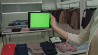 Woman's hand holding tablet computer with green screen in fashion store. Close-up. Chroma key