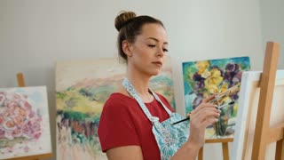 Young artist holding paintbrush and color palette while working on oil painting at studio.