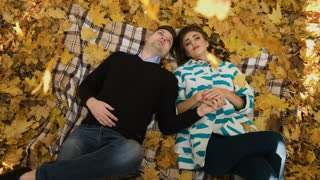 Young couple lying on a fallen autumn leaves in a park. Couple holding hands and talking. Shoot from above.