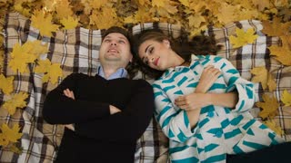 Young couple lying on a fallen autumn leaves in a park. man kissing woman's hand. Shoot from above.