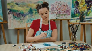 Young creative painter sitting at table full of tubes of paint and drawing on a piece of paper in art studio