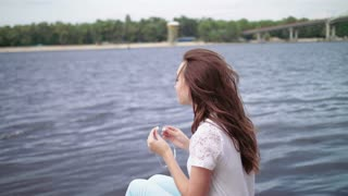 Young woman sitting by the river and listening to the music on smart phone. back view