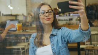 Young woman taking selfie photo with smart phone in cafe. Woman with coffee taking selfies. View through the window. Window view