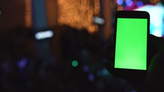 View from behind of hands hold smartphone with vertical green screen among people at rave party with light.