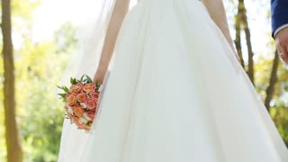 Wedding couple tenderly holding each other hands, bride holding bouquet of roses close up