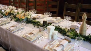White roses with greenery stand on the festive served dinner table