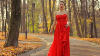 Woman in red dress and beautiful red fashionable shoes walking like a princess on the park.