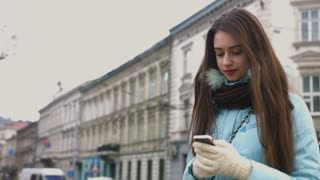 Woman using smartphone in the European city. Hipster girl browsing Internet on a phone, texting and communicating outdoors. Travel.