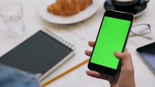 Woman using smartphone with green screen. Close-up video of woman's hands scrolling pages on mobile phone. Chroma key. Vertical
