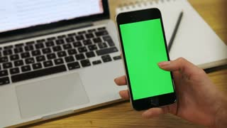 Woman using vertical smartphone with green screen. Close-up shot of woman's hands scrolling up mobile phone. Chroma key.