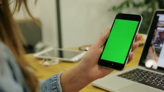 Woman watching video on smartphone with green screen. Close-up video of woman's hands holding mobile phone. Chroma key. Close up. Vertical