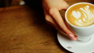 Women's hands puts a white cup of coffee on the table and then puts a spoon.
